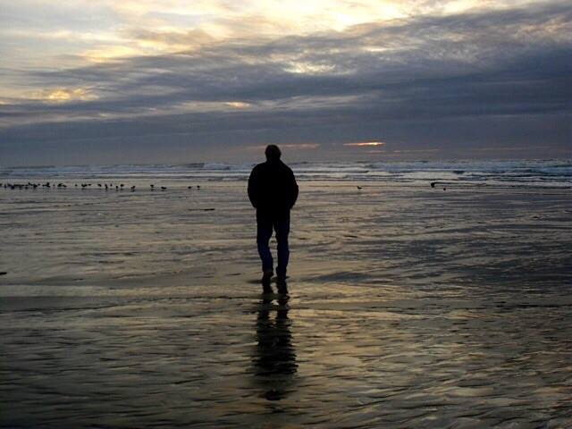 Photo of Man Walking on Beach in Silouette